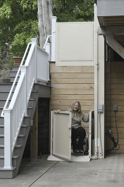 woman in wheelchair exiting Bruno vertical platform lift on the porch